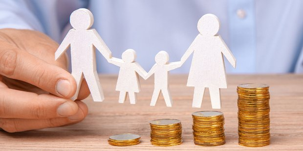 menschliche Hand hält eine Papierschablone einer vier köpfigen Familie über verschieden Große Stapel aus Münzen