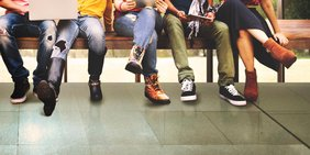 Junge Menschen mit Laptops auf einer Bank