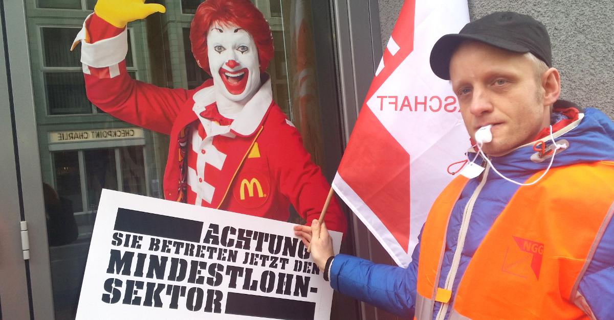"""Mann mit Schild """"Achtung! Sie betreten jetzt den Mindestlohn-Sektor"""" vor einem Bild von Ronald McDonald an einer McDonald's-Filiale"""