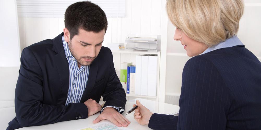 blonde Versicherungsverkäuferin im Beratungsgespräch mit einem Mann