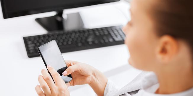 Frau mit Smartphone am Arbeitsplatz Büro