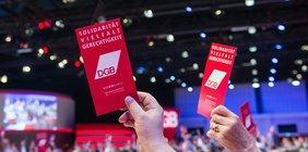 Hände halten rote Stimmkarten hoch