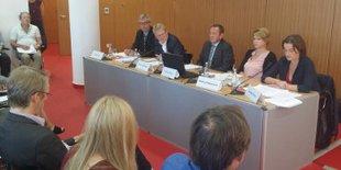 Podium einer Pressekonferenz mit fünf Personen; im Vordergrund Journalistinnen und Journalisten in Stuhlreihen