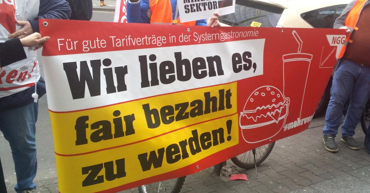 """Transparent mit der Aufschrift: """"Wir lieben es, fair bezahlt zu werden!"""""""
