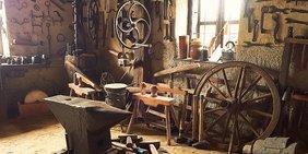 antike Werkstatt mit Wagenrad, Amboss und diversen Werkzeugen