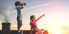 Zwei Kinder mit Fernglas auf einem Dach