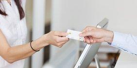 Patient reicht Arzthelferin eine Krankassenkarte
