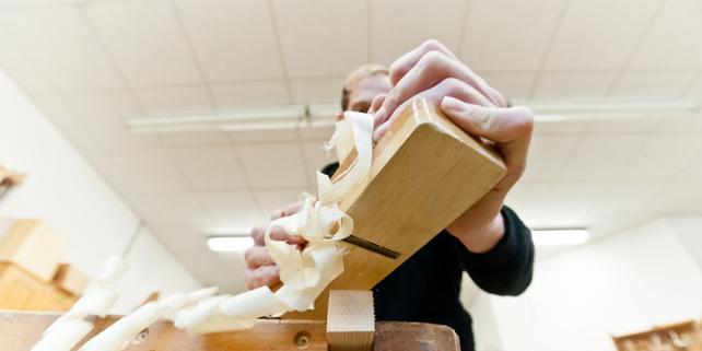 Tischler / Schreiner mit Hobel hobelt Holz, Holzspäne