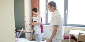 Krankenschwester und Pfleger stehen an Krankenbett