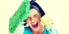 Schreiende Frau mit Putzutensilien