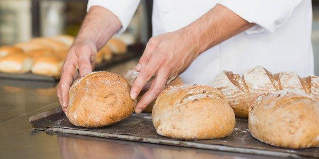 Bäckermeister packt frisches Brot auf ein Backblech mit anderen Broten