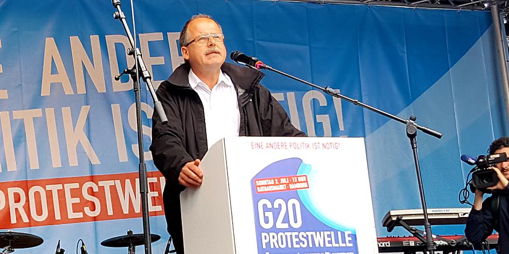 """DGB-Vorstand Stefan Körzell an Rednerpult auf Bühne; Pult mit Aufschrift """"G20-Protestwelle"""""""