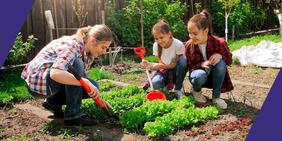 Frau erklärt Gartenarbeit am Beet mit zwei weiblichen Jugendlichen