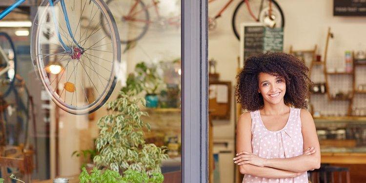 Junge Frau im Eingang von Fahrradgschäft