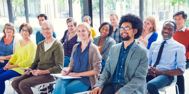 Fröhliche Menschen unterschiedlicher Herkunft im Publikum