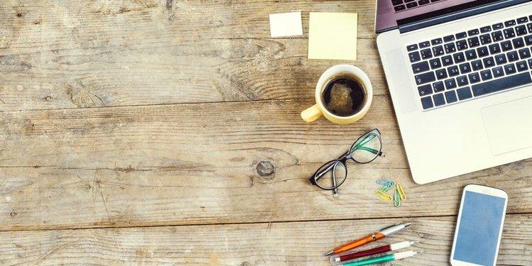 Schreibtisch mit Laptop, Smartphone, Notizzetteln und Stiften