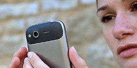 Junge Frau blickt auf ihr Smartphone
