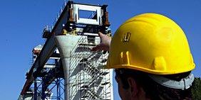 Bauarbeiter zeigt auf Brückenbaustelle
