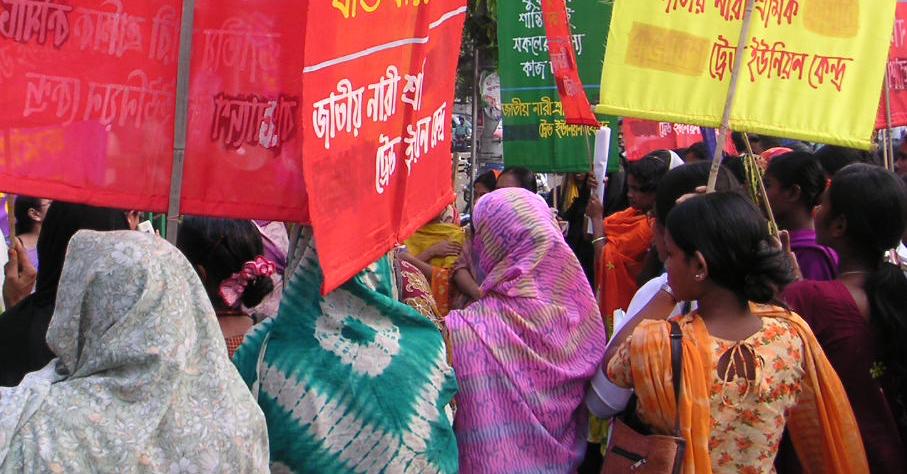 Frauen aus Bangladesch mit dem Rücken zur Kamera, die Protestbanner tragen