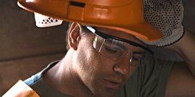 Bauarbeiter wischt Schweiß von Stirn