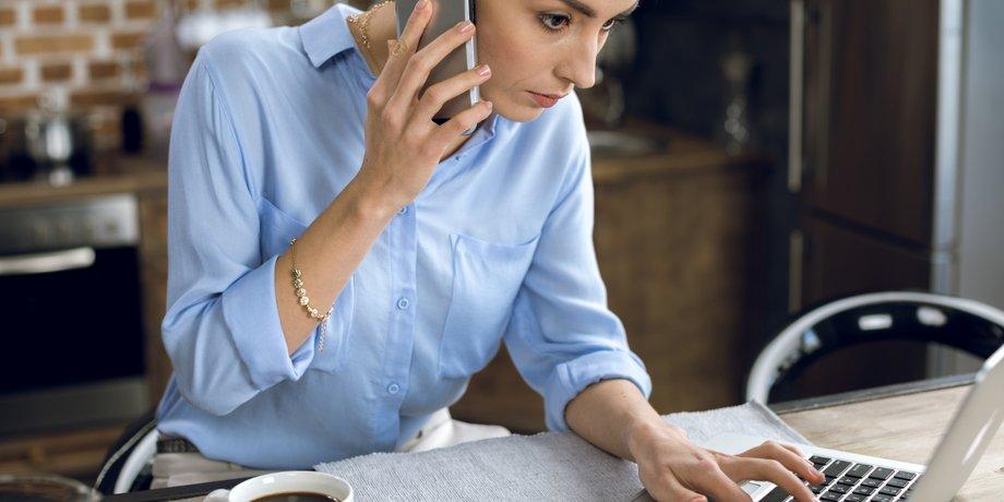 Frau am Küchentisch vor Laptop mit Handy am Ohr