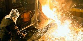 Stahlkocher im Schutzanzug vor Hochofen