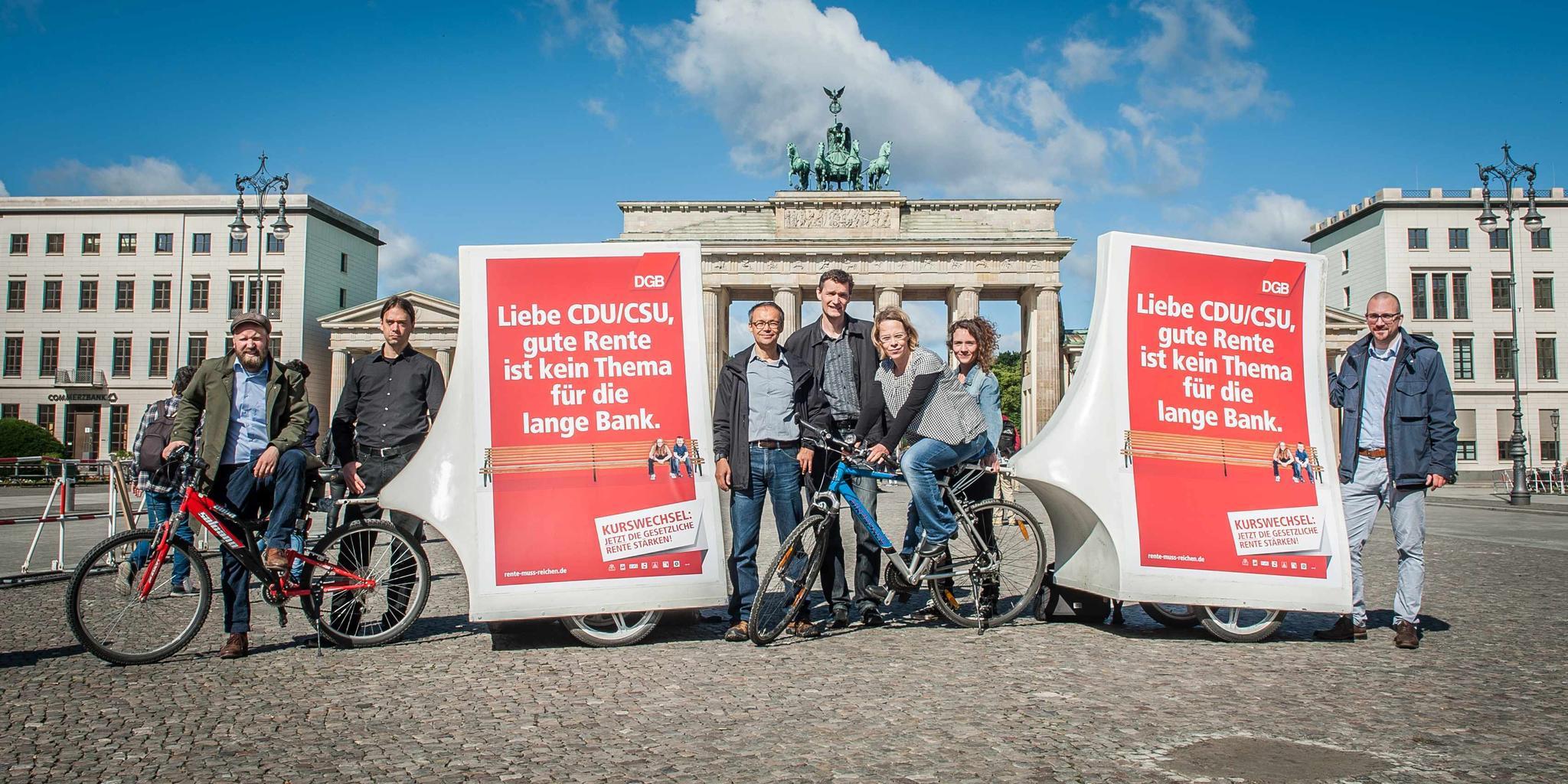 """Menschen mit Transparent """"Rente - Kurswechsel jetzt! Handeln statt Aussitzen"""" vor dem Brandenburger Tor"""