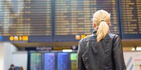 Frau mit schwarzer Lederjacke und blondem Pferdeschwanz steht vor Abflugterminal