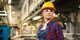 Junge Fabrikarbeiterin mir Helm