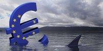 Großes Euro-Zeichen in Farben der europäischen Flagge versinkt im Wasser und eine Haifischflosse schaut heraus