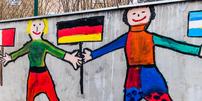 Malerei von Kindern auf Wand: Kinder mit Flaggen unterschiedlicher Länder Hand in Hand