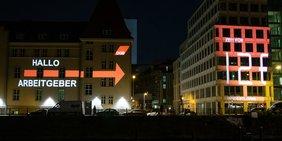 """Lichtaktion: Leuchtschrift """"Hallo Arbeitgeber, Zeit für 12 Euro Mindestlohn"""" an Hausfassade"""