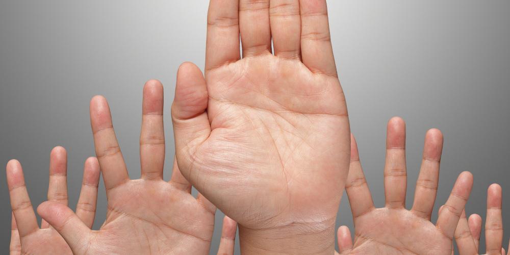 Hände, erhoben zur Abstimmung, grauer Hintergrund