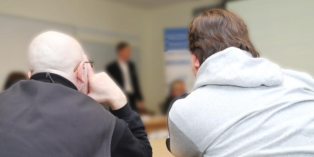 Zwei Männer (von hinten) in Seminarraum