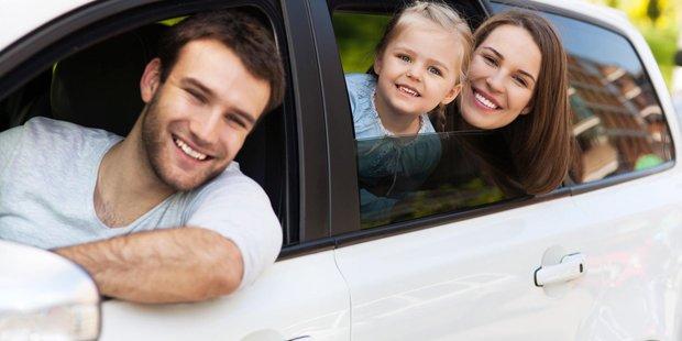 Drei köpfige Familie mit Vater, Tochter und Mutter sitzt im Auto und schaut aus dem Fenster