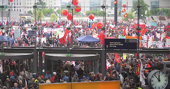 Menschenmassen im Foyer des Berliner Hauptbahnhof mir roten Luftballons und Plakaten