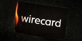 """Weißer Schriftzug """"Wirecard"""" auf einer schwarzen Kreditkarte oder Visitenkarte; Karte brennt"""