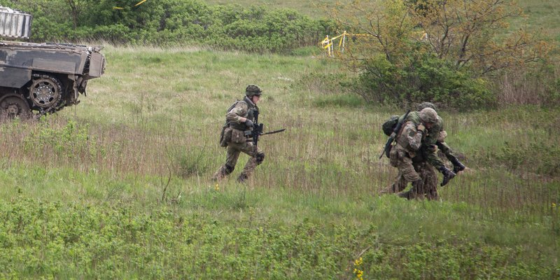 Wiese mit laufenden Soldaten, am Rand des Bildes ein Panzer