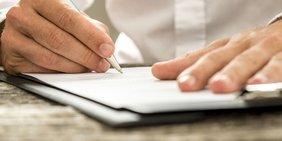 Hände mit Stift unterschreiben einen Vetrag