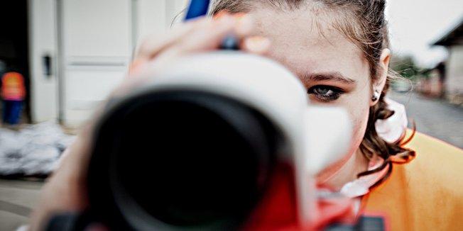 Junge Frau blickt durch Messgerät