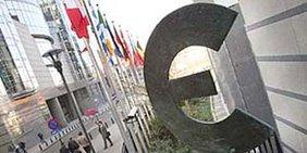 Eine Skulptur des Euro-Symbols in einer Straße mit Fahnenmasten