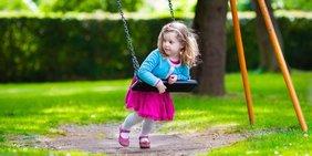 Kleines Mädchen an einer Schaukel