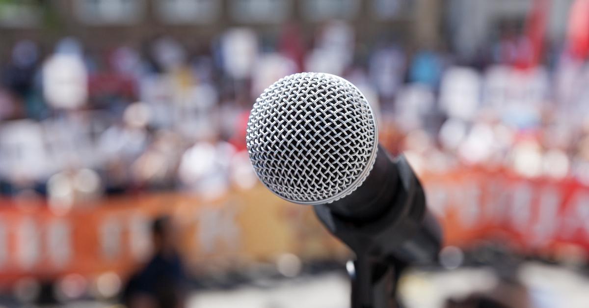 Nahaufnahme eines Mikrofons, im Hintergrund sehr unscharf eine Gruppe Demonstranten