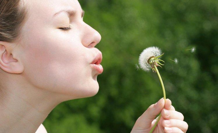 Frau mit Pusteblume auf einer Wiese