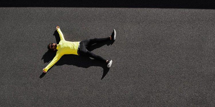 Läufer liegt erschöpft am Boden