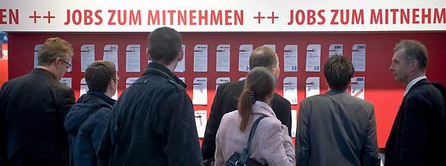 """Mehrere Menschen schauen auf eine Wand mit Stellenausschreibungen. Oben steht in roter Schrift """"Jobs zum Mitnehmen""""."""