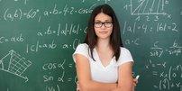 JUnge Frau steht vor Schultafel mit mathematischen Formeln