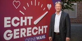 Reiner Hoffmann (DGB) vor Kampagnen-Motiv zur Bundestagswahl 2021