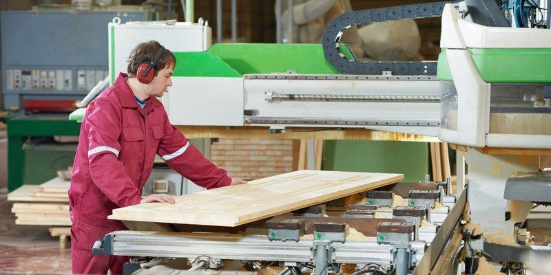 Tischler in einer Werkstatt an einer großen Maschine; schiebt Holzplatte entlang der Maschine