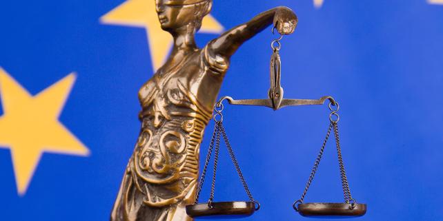 Kleine Statue von Justitia vor Fahne der EU